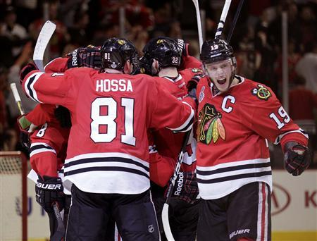 Chicago Blackhawks center Jonathan Toews (19) celebrates with his team after they defeated the Boston Bruins in triple-overtime in Game 1 of their NHL Stanley Cup Finals hockey series in Chicago, Illinois, June 13, 2013. REUTERS/John Gress