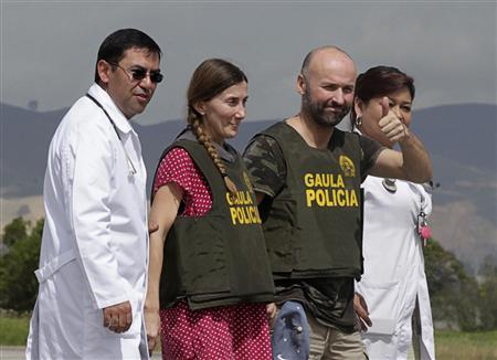 Spanish citizens Angel Fernandez Sanchez gestures to the media next to Maria Concepcion Marlaska after their arrival at the Catam military airport in Bogota June 15, 2013. REUTERS/Jose Miguel Gomez