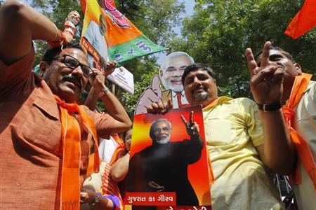Supporters of Gujarat's Chief Minister Narendra Modi celebrate while holding posters and cut-outs of Modi in the western Indian city of Ahmedabad June 9, 2013. REUTERS/Amit Dave