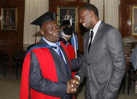 Jamaica's Olympic sprinter Usain Bolt (R) congratulates his coach Glen Mills after Mills received the degree of Doctor Honoris Causa from the University of the West Indies in Mona, November 3, 2012. REUTERS/Gilbert Bellamy