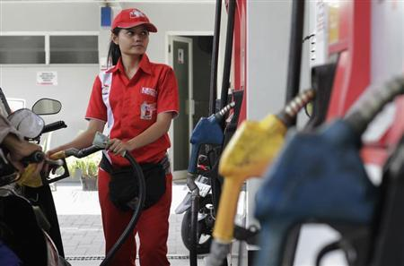 A petrol station attendant fills fuel into her customer's car at a petrol station in Jakarta April 30, 2013. REUTERS/Supri