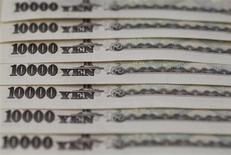 Купюры номиналом в 10.000 иен в Токио 28 февраля 2013 года. Курс иены снижается, но все еще близок к двухмесячным максимумам к доллару и евро, пока инвесторы ждут от ФРС новостей относительно стимулирующей программы. REUTERS/Shohei Miyano
