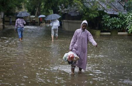 A woman carries vegetables as she walks though a flooded street during monsoon rains in Mumbai June 16, 2013. REUTERS/Danish Siddiqui