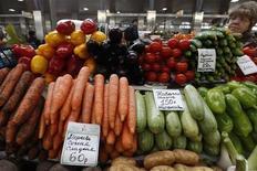 Женщина продает овощи на рынке в Санкт-Петербурге 5 апреля 2012 года. Минэкономразвития понизило прогноз инфляции в РФ в июне до 0,4-0,5 процента на фоне замедления роста цен на овощи, говорится в еженедельном мониторинге министерства, которое неделю назад ожидало инфляцию на уровне 0,5-0,6 процента за месяц. REUTERS/Alexander Demianchuk