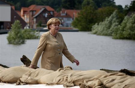 German Chancellor Angela Merkel walks on a dyke by the swollen river Elbe during a visit in Hitzacker June 12, 2013. REUTERS/Fabrizio Bensch