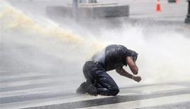 Водяная струя бьёт в участника демонстрации протеста, разгонямой полицией на площади Кизилай в Анкаре 16 июня 2013 года. Жесткая риторика Эрдогана не остудила пыл протестующих в Турции. REUTERS/Dado Ruvic