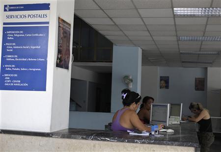 Cuban Postal Service workers sit at a post office in Havana June 17, 2013. REUTERS/Enrique De La Osa