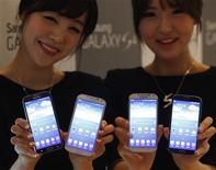 Unas modelos posan para una fotografía junto a unos teléfonos celulares S4 de Samsung en Seúl, abr 25 2013. Samsung Electronics tiene previsto vender una versión de su principal teléfono avanzado, el Galaxy S4, que transmita datos a casi dos veces la velocidad normal, dijo el lunes el responsable de la división de móviles. REUTERS/Kim Hong-Ji