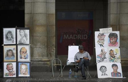 A caricaturist waits for costumers at Plaza Mayor square in Madrid June 17, 2013. REUTERS/Sergio Perez