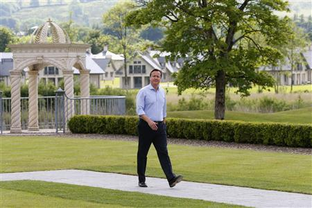 Britain's Prime Minister David Cameron walks toward his hosts arriving to the Lough Erne golf resort where the G8 summit is taking place in Enniskillen, Northern Ireland June 17, 2013. REUTERS/Yves Herman