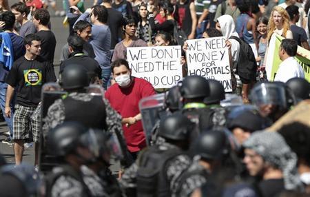 Activists demonstrate in front of riot police outside the Mane Garrincha National Stadium in Brasilia June 15, 2013. REUTERS/Ueslei Marcelino