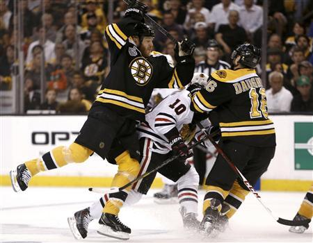 Boston Bruins' Shawn Thornton (22) and Kaspars Daugavins (16) collide with Chicago Blackhawks center Patrick Sharp (10) during the first period in Game 3 of their NHL Stanley Cup Finals hockey series in Boston, Massachusetts, June 17, 2013. REUTERS/Winslow Townson
