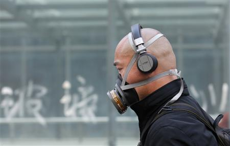 A man wearing a mask is seen on a street in Beijing in this May 2, 2013 file photograph. REUTERS/Kim Kyung-Hoon/Files