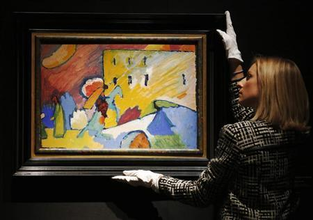 A Christie's employee poses with Wassily Kandinsky ''Studie zu 'Improvisation 3''' artwork at Christie's auction house in London June 7, 2013. The artwork, with an estimated value of 15 million pounds Sterling (U.S. dollars 23.25 million), forms part of an exhibition ''Masterpieces at Christie's'' which commences the summer auction season. REUTERS/Luke MacGregor