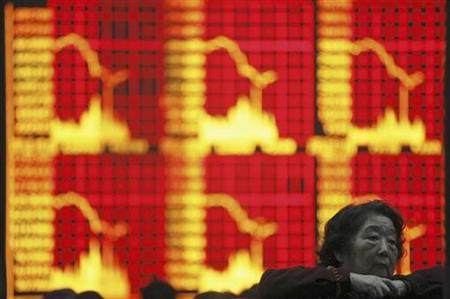An investor gestures in front of an electronic board showing stock information at a brokerage house in Shanghai, November 30, 2010. REUTERS/Stringer/Files