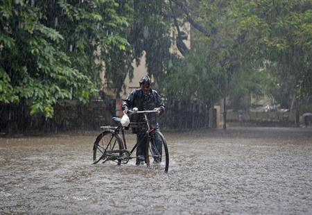 A man pushes his bicycle though a flooded street during monsoon rains in Mumbai June 16, 2013. REUTERS/Danish Siddiqui