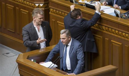 Anatoly Myarkovsky (C), first deputy finance minister, delivers a speech while opposition deputies react next to speaker's rostrum during a session of the parliament in Kiev June 18, 2013. REUTERS/Stringer