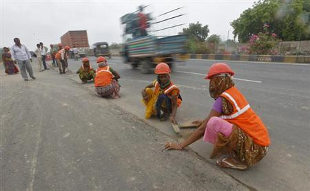 Workers clean the sides of a road before building a highway on the outskirts of Ahmedabad June 18, 2013. REUTERS/Amit Dave/Files
