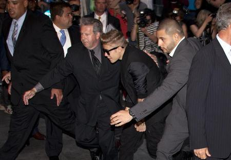 Singer Justin Bieber (C) arrives late for the premiere of the film ''After Earth'' in New York May 29, 2013. REUTERS/Carlo Allegri