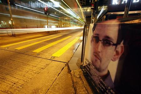 A bus passes by a poster of Edward Snowden, a former contractor at the National Security Agency (NSA), displayed by his supporters at Hong Kong's financial Central district during the midnight hours of June 18, 2013, while Snowden is engaged in a live chat online believed to be in Hong Kong. REUTERS/Bobby Yip