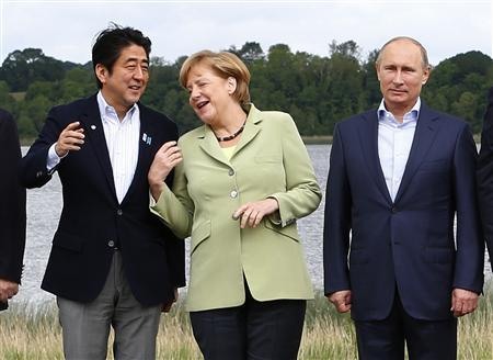Japan's Prime Minister Shinzo Abe (L), German Chancellor Angela Merkel (C) and Russia's President Vladimir Putin take part in a group photo at the G8 Summit, at Lough Erne, near Enniskillen, in Northern Ireland June 18, 2013. REUTERS/Yves Herman