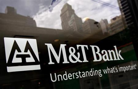Buildings are reflected in the window of an M&T Bank branch in New York August 27, 2012. REUTERS/Brendan McDermid