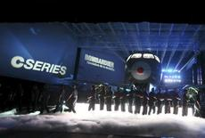 Bombardier employees form a line as the CS300 aircraft is unveiled at a news conference at its assembly facility in Mirabel, Quebec, March 7, 2013. REUTERS/Christinne Muschi
