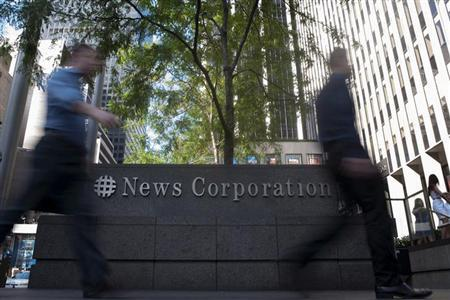 Passers-by walk near the News Corporation building in New York June 28, 2012. REUTERS/Keith Bedford
