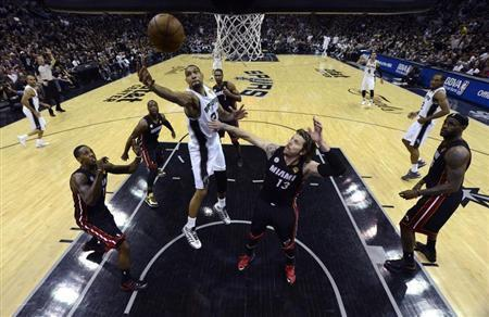 San Antonio Spurs power forward Tim Duncan (21) goes to the basket past Miami Heat shooting guard Mike Miller (13) during Game 5 of their NBA Finals basketball series in San Antonio, Texas, June 16, 2013. REUTERS/Brendan Maloney/Pool