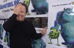 "Actor Billy Crystal, voice talent of character Mike Wazowski in the new computer animated film ""Monsters,Inc."" mimics his characters appearance next to a poster as he arrives at the film's premiere in Hollywood October 28, 2001. REUTERS/Fred Prouser"