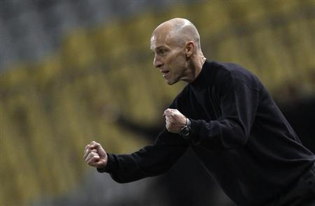 Egypt's head coach Bob Bradley of the U.S. celebrates after Mohamed Aboutriaka scored against Zimbabwe during their 2014 World Cup qualifying soccer match at Borg El Arab ''Army Stadium'', west of the Mediterranean city of Alexandria, 230 km (143 miles) north of Cairo, March 26, 2013. REUTERS/Amr Abdallah Dalsh