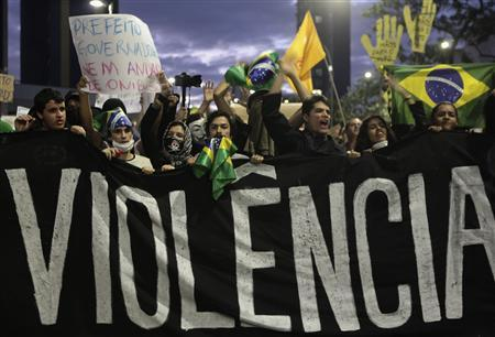 Demonstrators shout anti-government slogans behind a banner, which reads as 'violence', during one of many protests around Brazil's major cities in Sao Paulo June 17, 2013. REUTERS/Alex Almeida