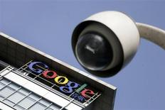 The Google logo is seen on the top of its China headquarters building behind a road surveillance camera in Beijing January 26, 2010. REUTERS/Jason Lee