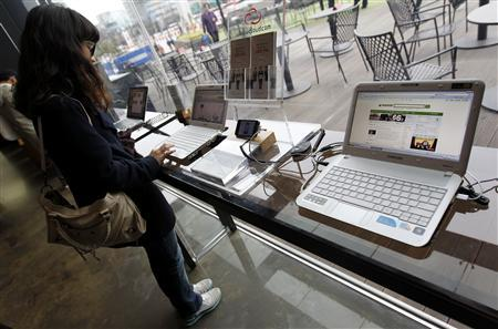 A woman surfs the Internet on a computer for visitors at a registration desk at South Korean mobile carrier KT's headquarters in Seoul December 2, 2011. REUTERS/Jo Yong-Hak