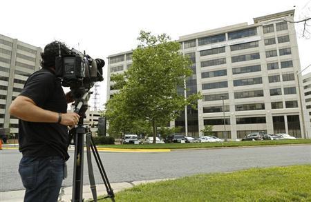 A news cameraman trains his lens on the Booz Allen Hamilton Holding Corp. building in McLean, Virginia June 11, 2013. REUTERS/Kevin Lamarque