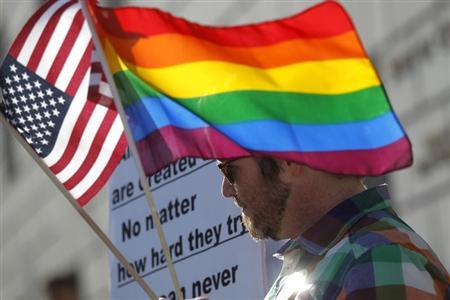 A man carries flags at a rally in support of same-sex marriage at the State of California Supreme Court in San Francisco, California March 26, 2013. REUTERS/Robert Galbraith
