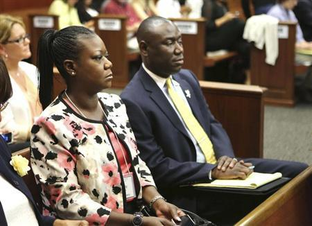 Sybrina Fulton, the mother of slain teen Trayvon Martin, sits with family attorney Benjamin Crump, during proceedings in the trial of George Zimmerman in Seminole Circuit Court in Sanford, Florida, June 17, 2013. REUTERS/Joe Burbank/Pool