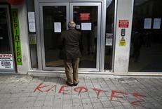 A depositor waits to enter a Laiki Bank branch in Nicosia March 28, 2013. REUTERS/Yannis Behrakis