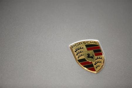 A logo is seen on a Porsche 911 Carrera 4S displayed ahead of the annual news conference at the Porsche headquarters in Stuttgart March 15, 2013. REUTERS/Lisi Niesner