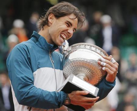 Rafael Nadal of Spain bites the trophy after defeating compatriot David Ferrer in their men's singles final match to win the French Open tennis tournament at the Roland Garros stadium in Paris June 9, 2013. REUTERS/Gonzalo Fuentes