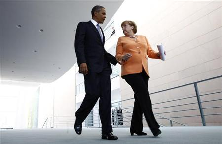 U.S. President Barack Obama and German Chancellor Angela Merkel (R) make their way to a news conference at the Chancellery in Berlin June 19, 2013. REUTERS/Thomas Peter