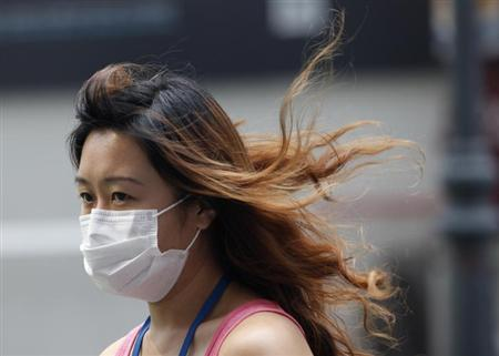 A woman wearing a face mask walks in the hazy central business district of Singapore June 19, 2013. REUTERS/Edgar Su