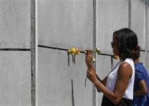 U.S. first lady Michelle Obama (L) and her daughter Sasha place flowers as they visit the Berlin Wall memorial in Bernauer Strasse in Berlin June 19, 2013. REUTERS/Tobias Schwarz