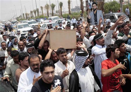 Iraqi mourners carry the coffin of Dhia Mutasharm, a Shi'ite militia fighter killed in clashes with the Free Syrian Army, during a funeral in Basra, 420 km (261 miles) southeast of Baghdad in this May 6, 2013 file photo. REUTERS/Atef Hassan/Files