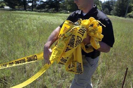 A federal investigator carries yellow crime tape at a field which investigators are prepared to dig up for the remains of former Teamsters boss Jimmy Hoffa in Oakland Township, Michigan June 17, 2013. REUTERS/ Rebecca Cook