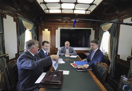 Russia's President Vladimir Putin meets with CEO of Russian Railways Vladimir Yakunin (L), Deputy Prime Minister Arkady Dvorkovich (2nd L) and Transport Minister Maxim Sokolov (R) inside a train in Moscow October 19, 2012. REUTERS/Alexsey Druginyn/RIA Novosti/Pool