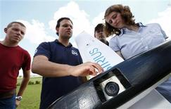 "Michael Niesen (2nd L) of MAVinci explains the camera equipped ""Sirius"" unmanned aerial vehicle (UAV) during a training session for clients on an airfield for model aircraft in Walldorf near Heidelberg, June 13, 2013. REUTERS/Ralph Orlowski"