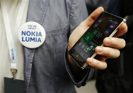 A worker poses with the Nokia Lumia 925 at its launch in London May 14, 2013. REUTERS/Luke MacGregor