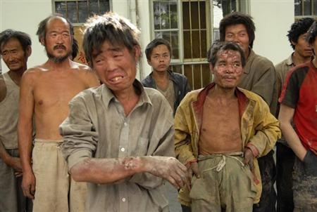 Workers stand at a police station after they were rescued from a brickworks in Hongdong County in Linfen, north China's Shanxi province, May 27, 2007. Thirty-one people, forced to work for a year as slaves -- given only bread and water and no pay -- were rescued at a brickworks run by the son of a local Communist Party official, state media reported on June 8, 2007. Picture taken May 27, 2007. REUTERS/China Daily