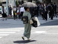 "A woman in a traditional ""Kimono"" carries shopping bags at a shopping district in Tokyo May 19, 2011. REUTERS/Kim Kyung-Hoon"